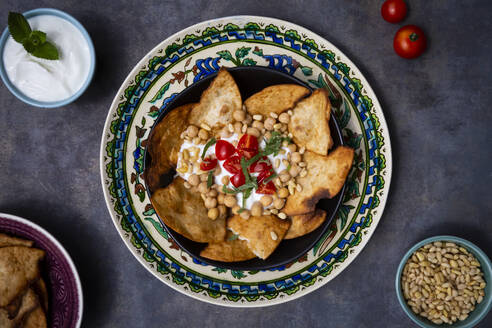 Bowl of Levantine fatteh, with flat bread, tomatoes and chickpeas - LVF08309
