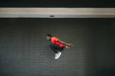 Young sportive man jumping in front of a brick wall - OCMF00764