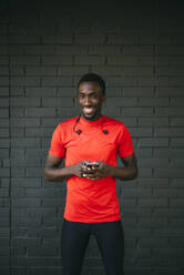 Portrait of a smiling young sportive man standing in front of a brick wall using his smartphone - OCMF00767
