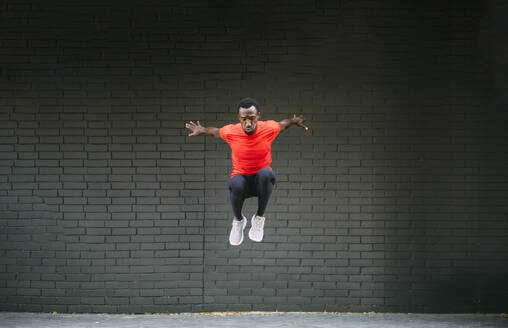Young sportive man jumping in front of a brick wall - OCMF00770