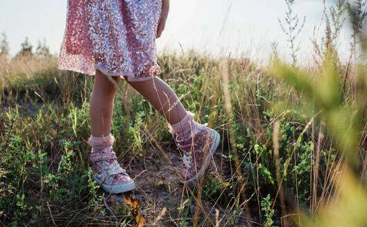 Young girls sparkly shoes and dress in the middle of a field at sunset - CAVF64590