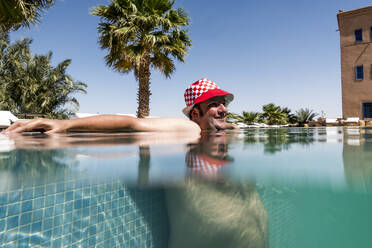 Overweight man with hat bathing in pool - OCMF00780