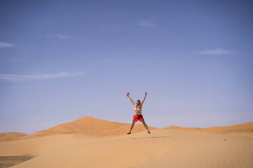 Overweight man with swimming shorts jumping in the desert of Morocco - OCMF00786