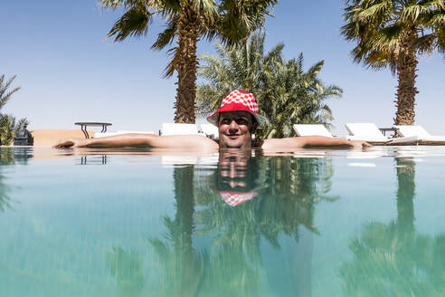Overweight man with hat bathing in pool - OCMF00789