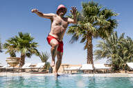 Overweight man jumping into swimming pool - OCMF00792