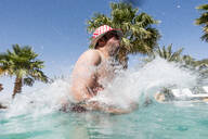 Overweight man jumping into swimming pool - OCMF00795