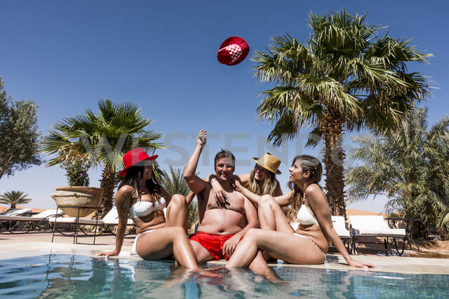 Overweight man surrounded by affectionate beautiful women at the poolside - OCMF00798 - Oscar Carrascosa Martinez/Westend61