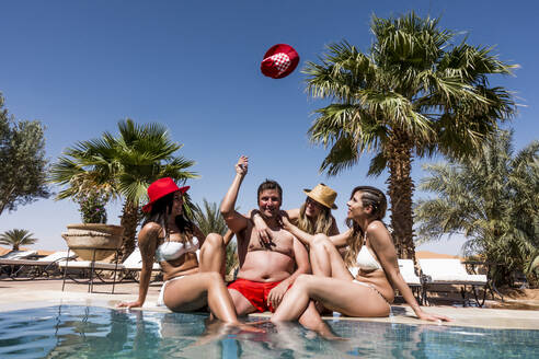Overweight man surrounded by affectionate beautiful women at the poolside - OCMF00798