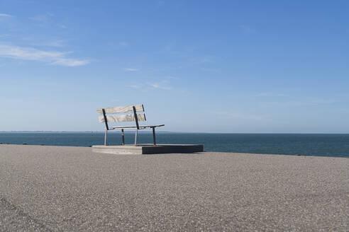 Netherlands, Zeeland, Veere, Westenshouwen, bench overlooking tranquil sea - CHPF00591