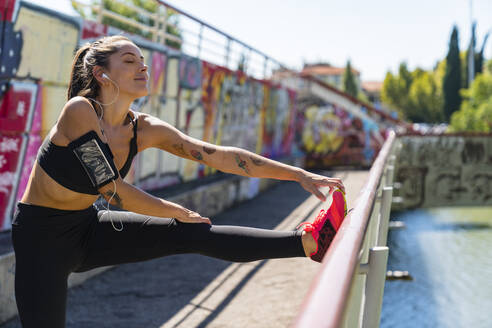 Young woman stretching on a bridge - MGIF00744