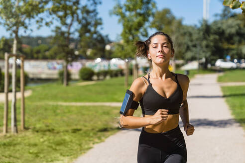 Portrait of young woman running in a park - MGIF00747