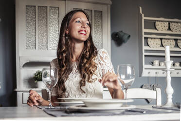 Portrait of smiling young woman sitting at laid table in country style kitchen - WFF00106