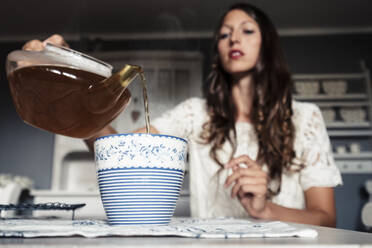 Young woman pouring tea into cup - WFF00109