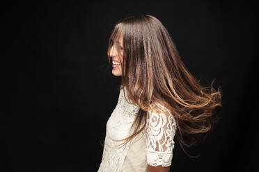 Happy young woman with long brown hair against black background - WFF00115