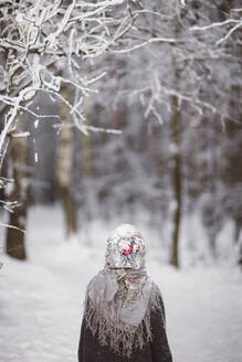 Back view of little girl wearing headscarf standing in front of winter forest - EYAF00495