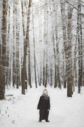Smiling little girl standing in front of winter forest - EYAF00498