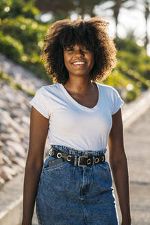 Portrait of smiling young woman with smartphone in her pocket - MPPF00051