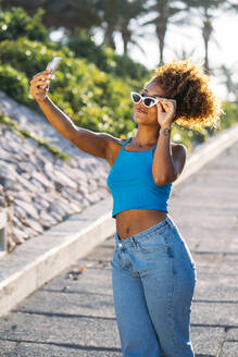 Portrait of young woman with sunglasses taking selfie with smartphone - MPPF00057