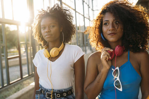 Portrait of two young women with headphones at sunset - MPPF00081