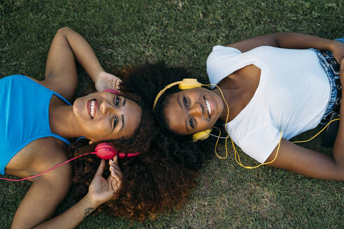 Portrait of two happy young women lying on meadow listening music with headphones - MPPF00087