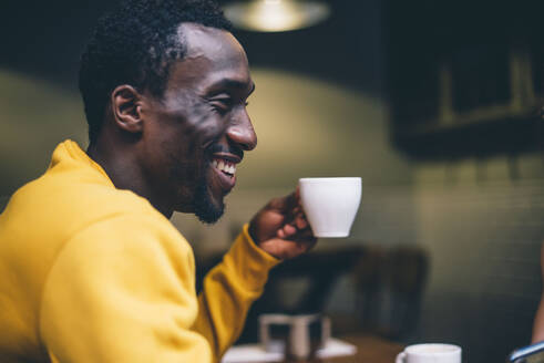 Laughing man with cup of coffee in a coffee shop - CJMF00046