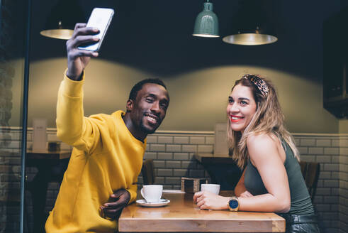 Portrait of smiling couple in a coffee shop taking selfie with smartphone - CJMF00049