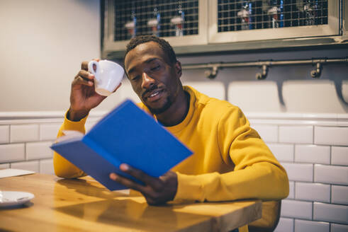 Portrait of man in a coffee shop reading a book - CJMF00064