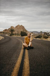 Woman sitting on road, Joshua Tree National Park, California, USA - LHPF01011