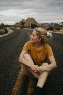Woman sitting on road, Joshua Tree National Park, California, USA - LHPF01014