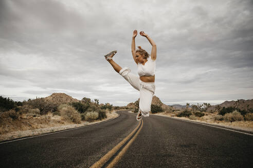 Woman jumping on road, Joshua Tree National Park, California, USA - LHPF01017