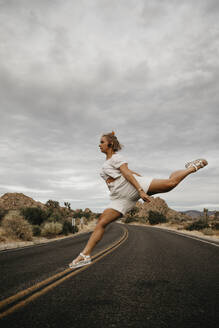 Woman jumping on road, Joshua Tree National Park, California, USA - LHPF01020
