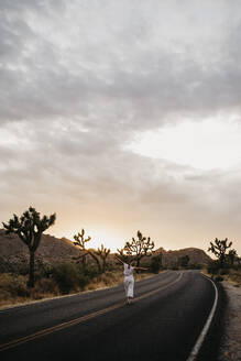 Woman walking on road at sunset, Joshua Tree National Park, California, USA - LHPF01023