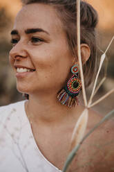 Portrait of smiling woman with earring and twigs, Joshua Tree National Park, California, USA - LHPF01026