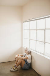 Young woman sitting on the floor in a room - LHPF01029