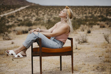 Woman sitting on a chair in desert landscape, Joshua Tree National Park, California, USA - LHPF01041