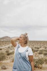 Young woman standing in desert landscape, Joshua Tree National Park, California, USA - LHPF01047