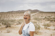 Portrait of laughing young woman in desert landscape, Joshua Tree National Park, California, USA - LHPF01053