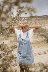 Happy young woman standing in desert landscape covering her eyes, Joshua Tree National Park, California, USA - LHPF01056