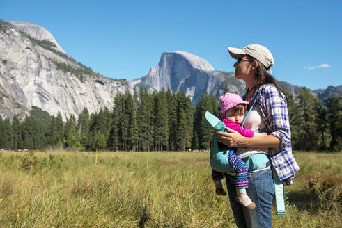 Mother carrying daughter in baby carrier, Yosemite National Park, California, USA - GEMF03197