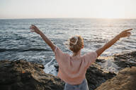Rear view of young woman at the sea with raised arms, Sunset Cliffs, San Diego, California, USA - LHPF01067