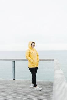 Young woman wearing yellow rain coat - NAF00118
