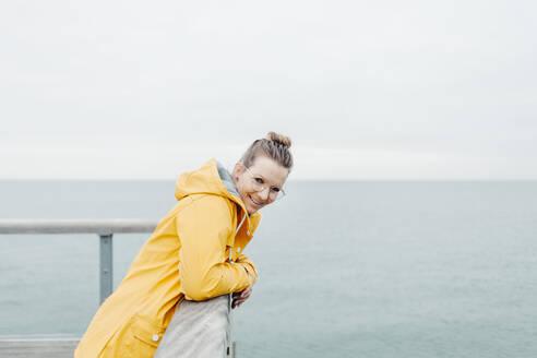 Young woman wearing yellow rain coat - NAF00121