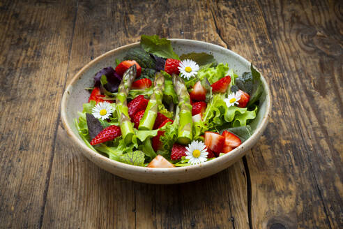 Close-up of salad with green asparagus, strawberries and daisies - LVF08317