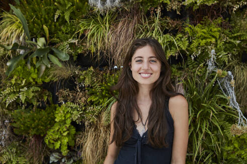 Portrait of smiling young woman in front of plant wall - SUF00597