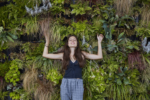 Portrait of smiling young woman with closed eyes in front of plant wall - SUF00603