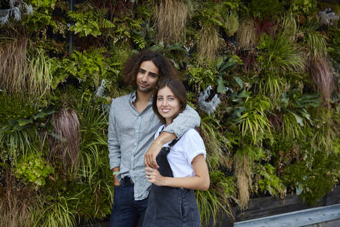 Portrait of smiling young couple in front of plant wall - SUF00606