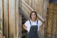 Portrait of smiling young woman in front of wooden fence - SUF00609