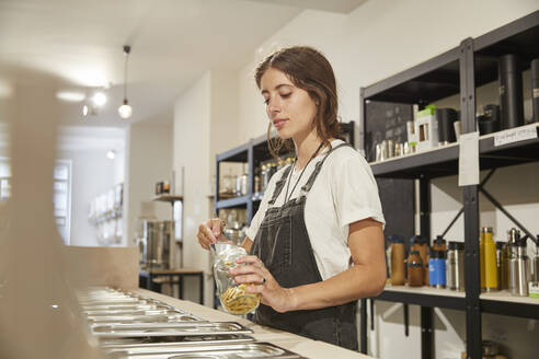 Young woman in packaging-free supermarket filling pasta into jar - SUF00627