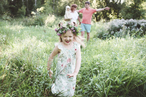 Happy little girl with flower wreath running from her parents in nature - EYAF00513