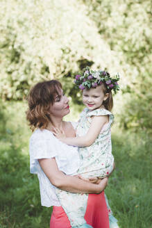 Mother holding daughter with flower wreath - EYAF00519